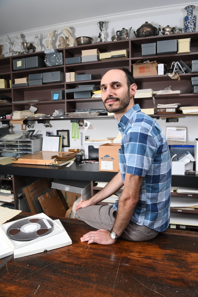 Portrait of Matt Testa, one of the authors of this blog post, seated on a table in the archives of the Peabody Institute surrounded by collection objects.