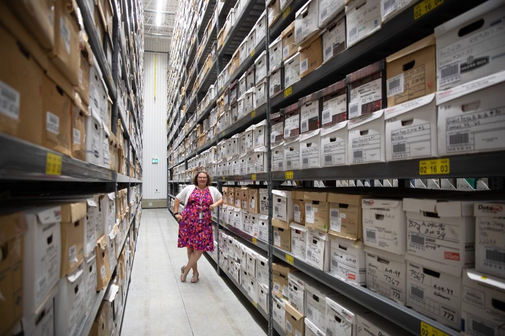 Heather Bidzinski stands among archives stacks, with bankers boxes surrounding.