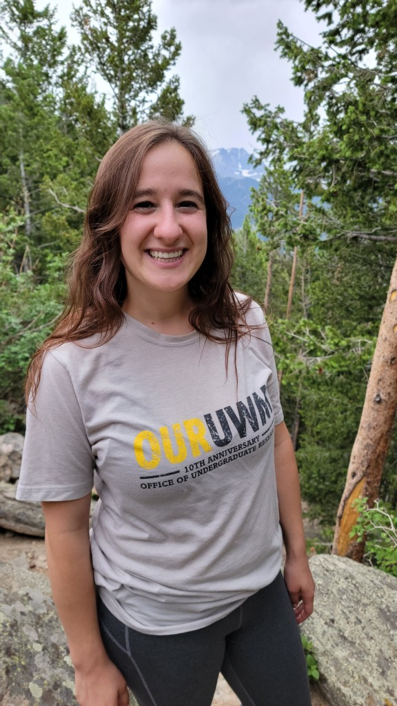 Photograph of archivist Nora Plant wearing OurUWM t-shirt with forest in the background.