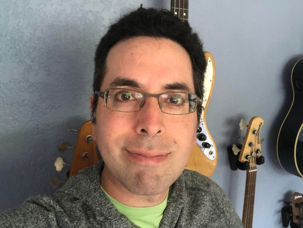 Headshot of Erik R. Bauer, with guitars hanging on the wall