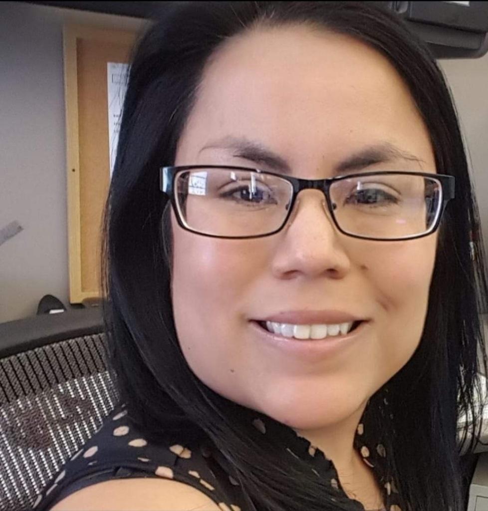 Headshot of Jennifer Olguin, sitting at a desk chair