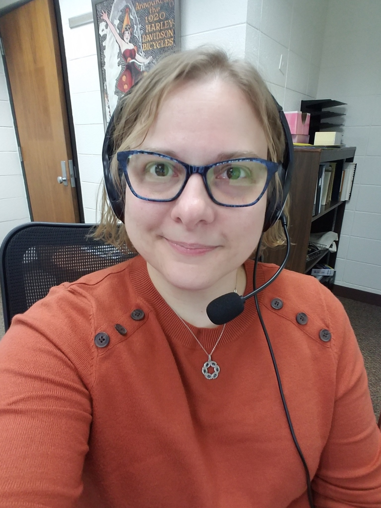 Photo of archivist Jennifer Motszko seated in an office chair with her headset on.